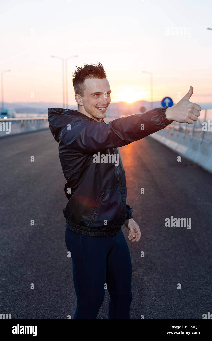 Half Body Shot of a Smiling Fit Guy at the hifgway sunset, Showing Thumbs up - Stock Image