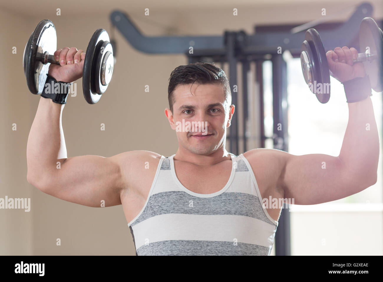 Athlete muscular bodybuilder man demonstrates his muscles in the gym - Stock Image