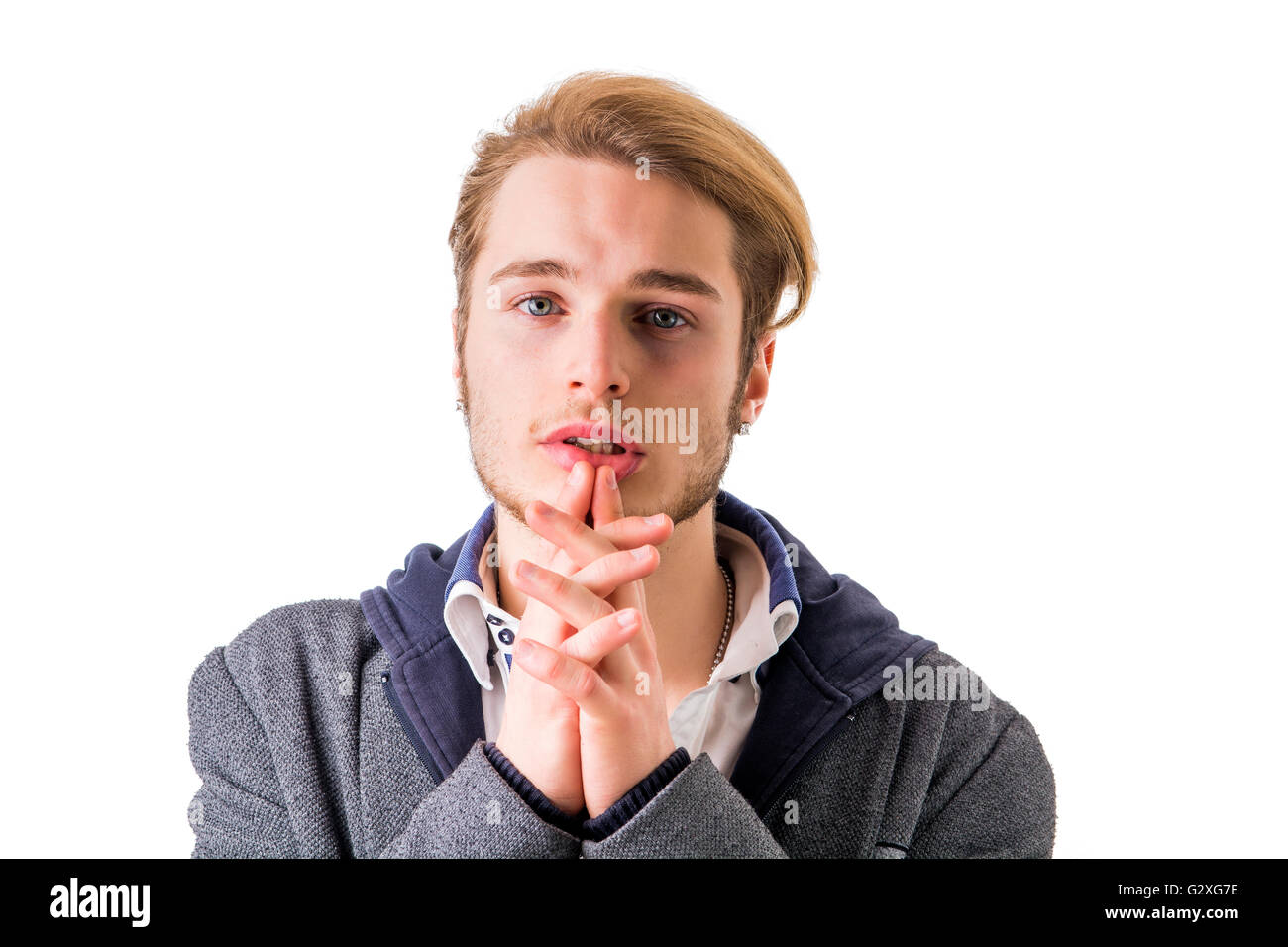 Needy, desperate young man pleading with hands joined as if praying to camera, isolated - Stock Image