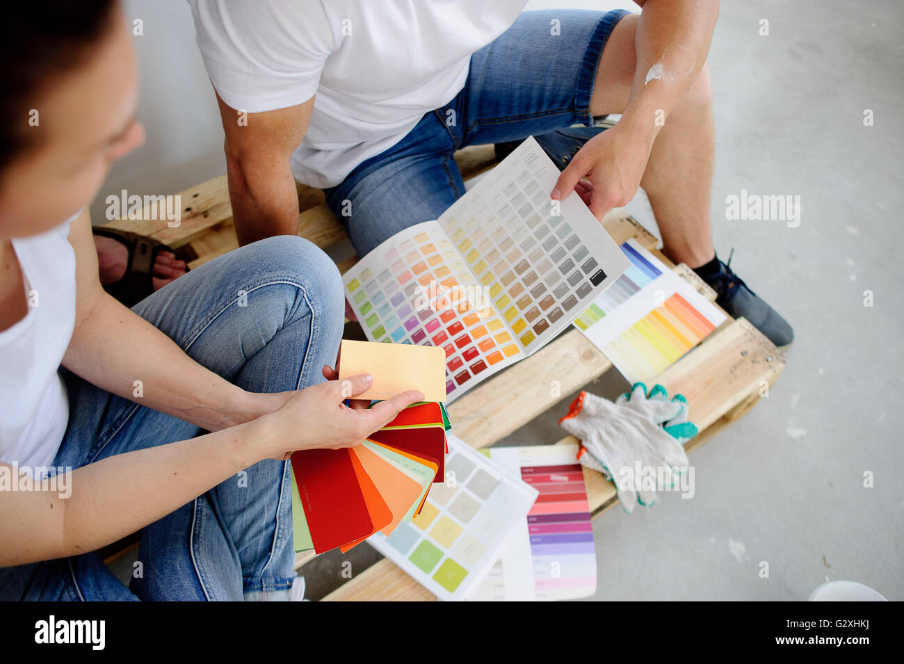 Two Persons Choose Color Of Decor Sitting On The Wooden