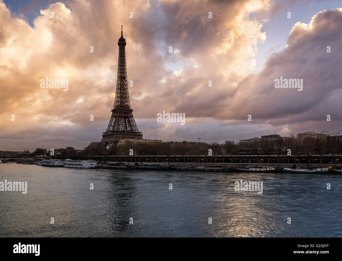 Luminous clouds the Eiffel Tower and the Seine River at sunrise. Port de Suffren, Paris, France - Stock Image