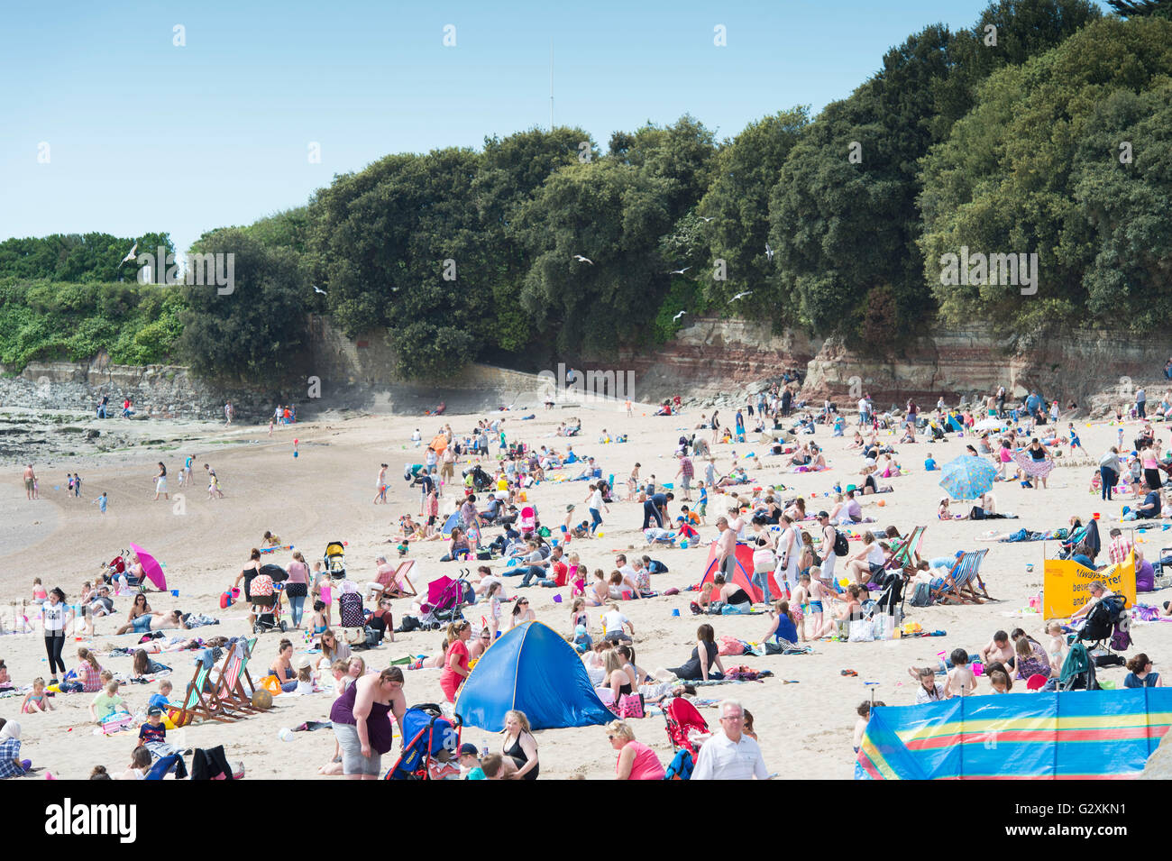 A busy Whitmore Bay beach at Barry Island, Barry, South Wales on a warm summers day. - Stock Image