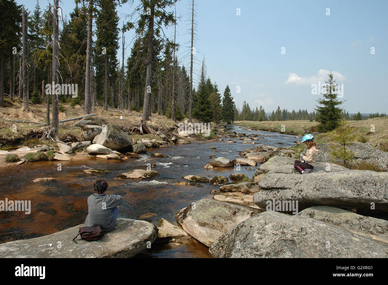 JAKUSZYCE, POLAND - APRIL 30: Unidentified woman and kid resting on rocks on river bank in izerskie mountains in - Stock Image