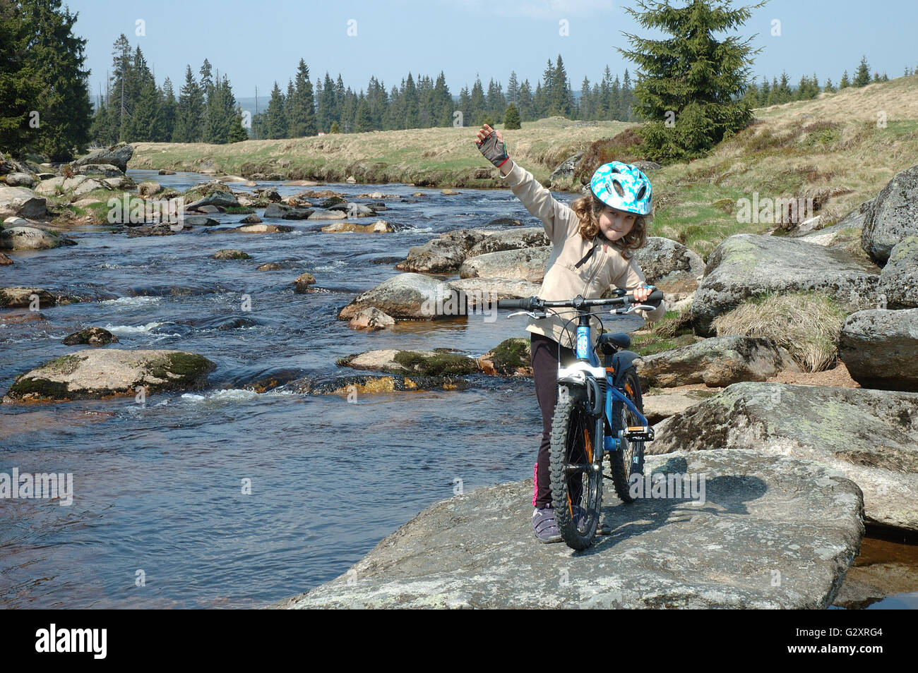 JAKUSZYCE, POLAND - APRIL 30: Unidentified little girl with bicycle on river bank in izerskie mountains in Poland - Stock Image