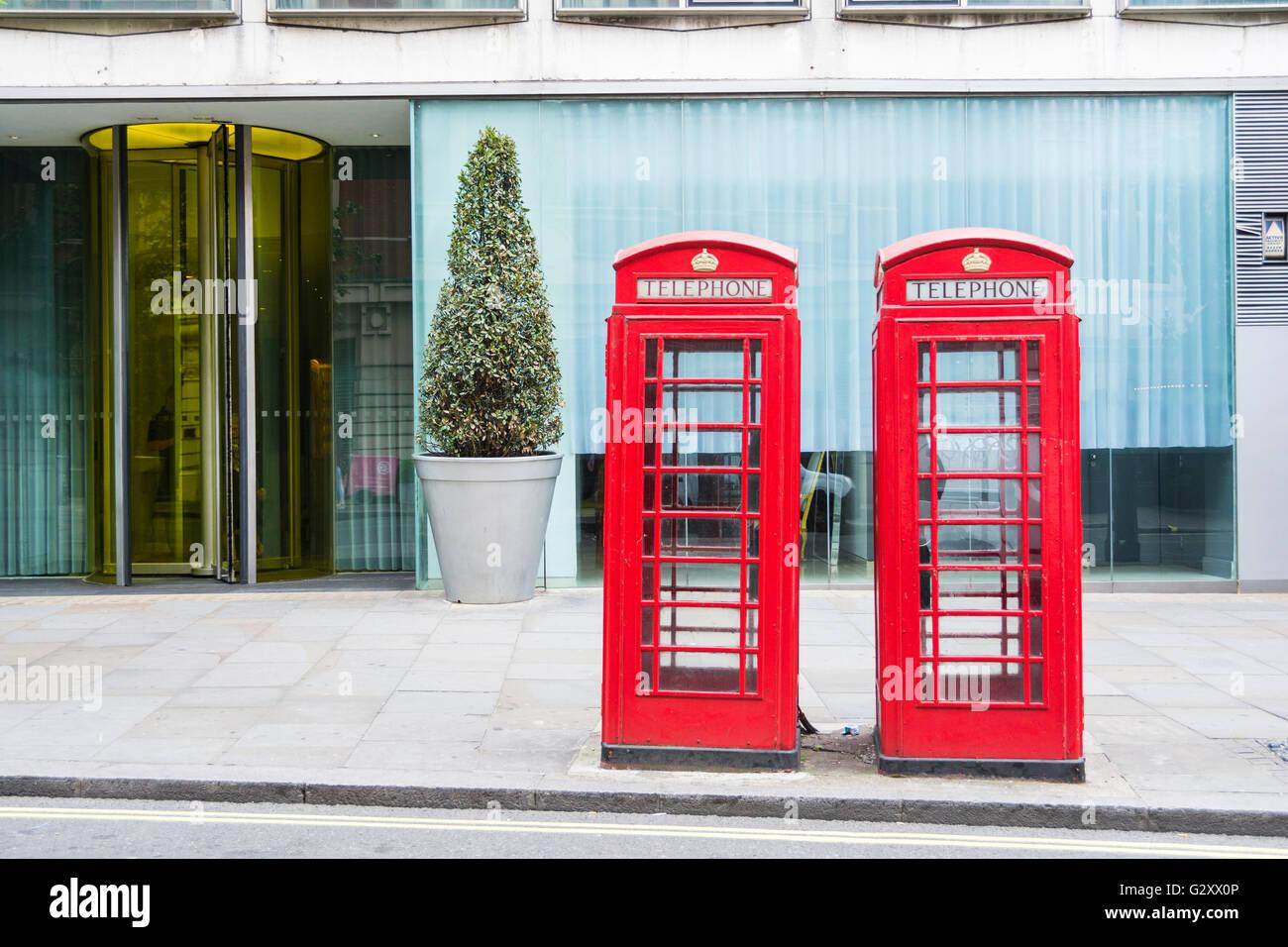Two bright red K6 London telephone kiosks on London's St Martins Lane. - Stock Image