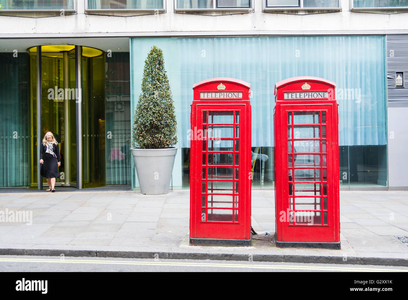 A woman emerges from an office door behind two bright red grade II listed Giles Gilbert Scott K6 London telephone - Stock Image
