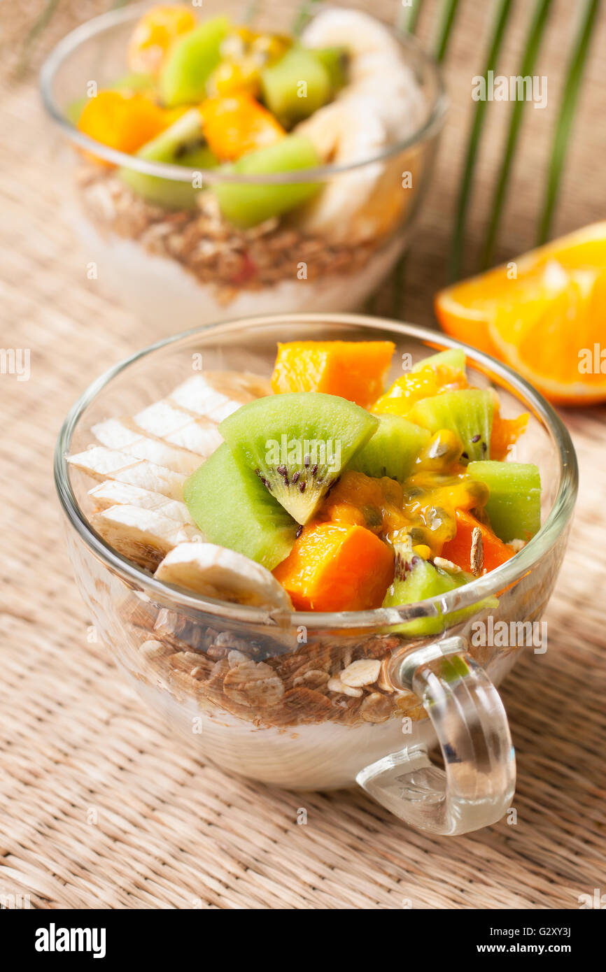 Dietary breakfast. Muesli, yoghurt, tropical fruits: mango, kiwi, pineapple, passion fruit in cup on a straw background - Stock Image
