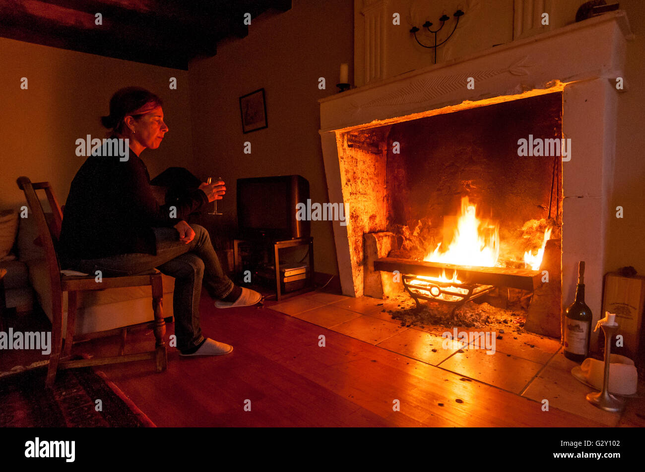 A woman enjoys the warmth and comfort of a roaring log fire. - Stock Image