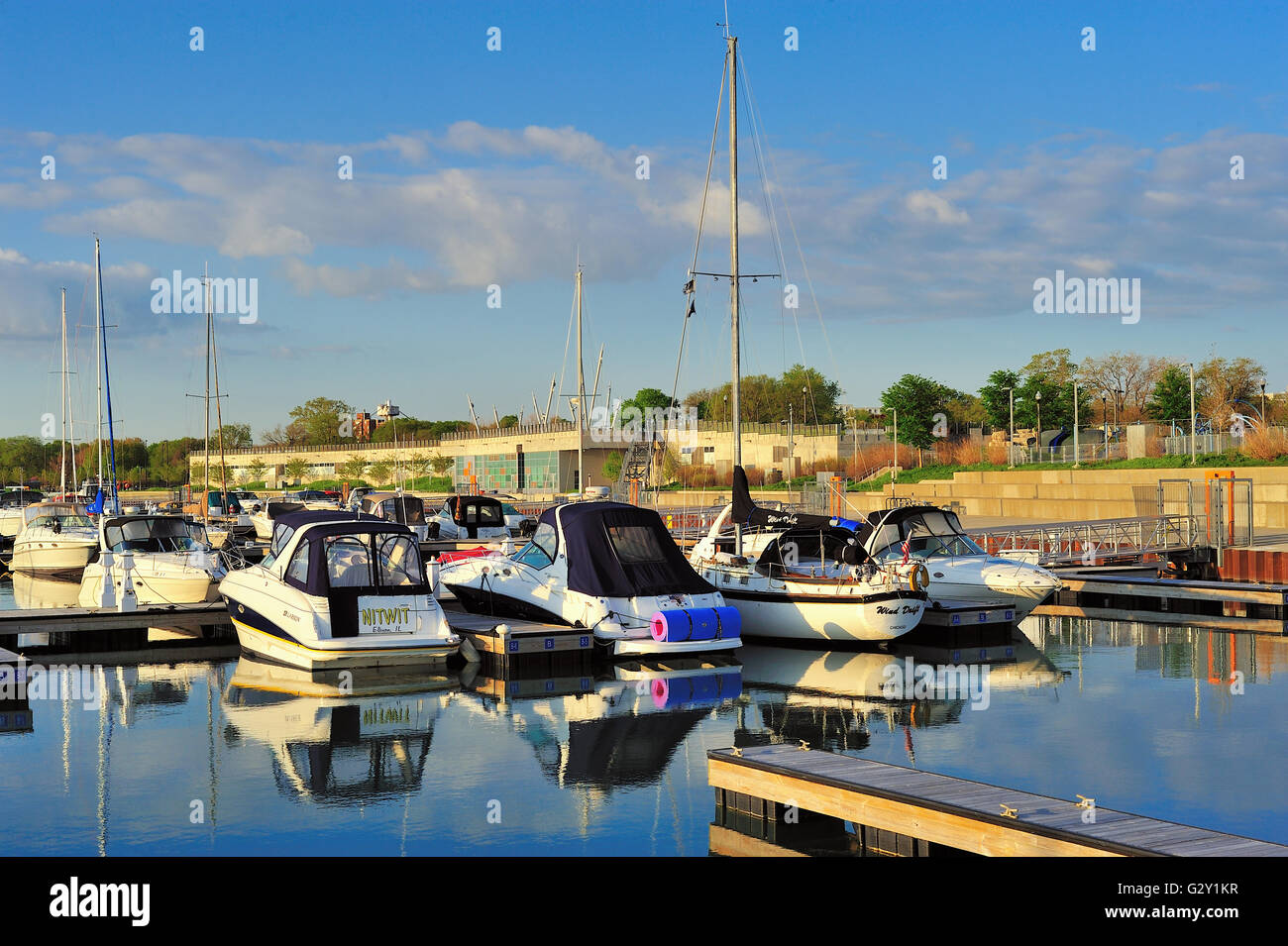 Shortly after sunrise, calm water in Chicago's 31st Street Harbor provides reflections of pleasure craft in - Stock Image