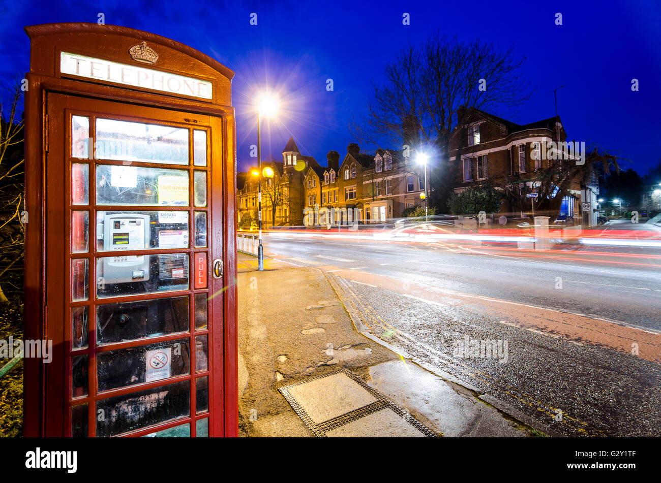 Night scene in Cambridge, UK, with red telephone box and motion blur light trails - Stock Image