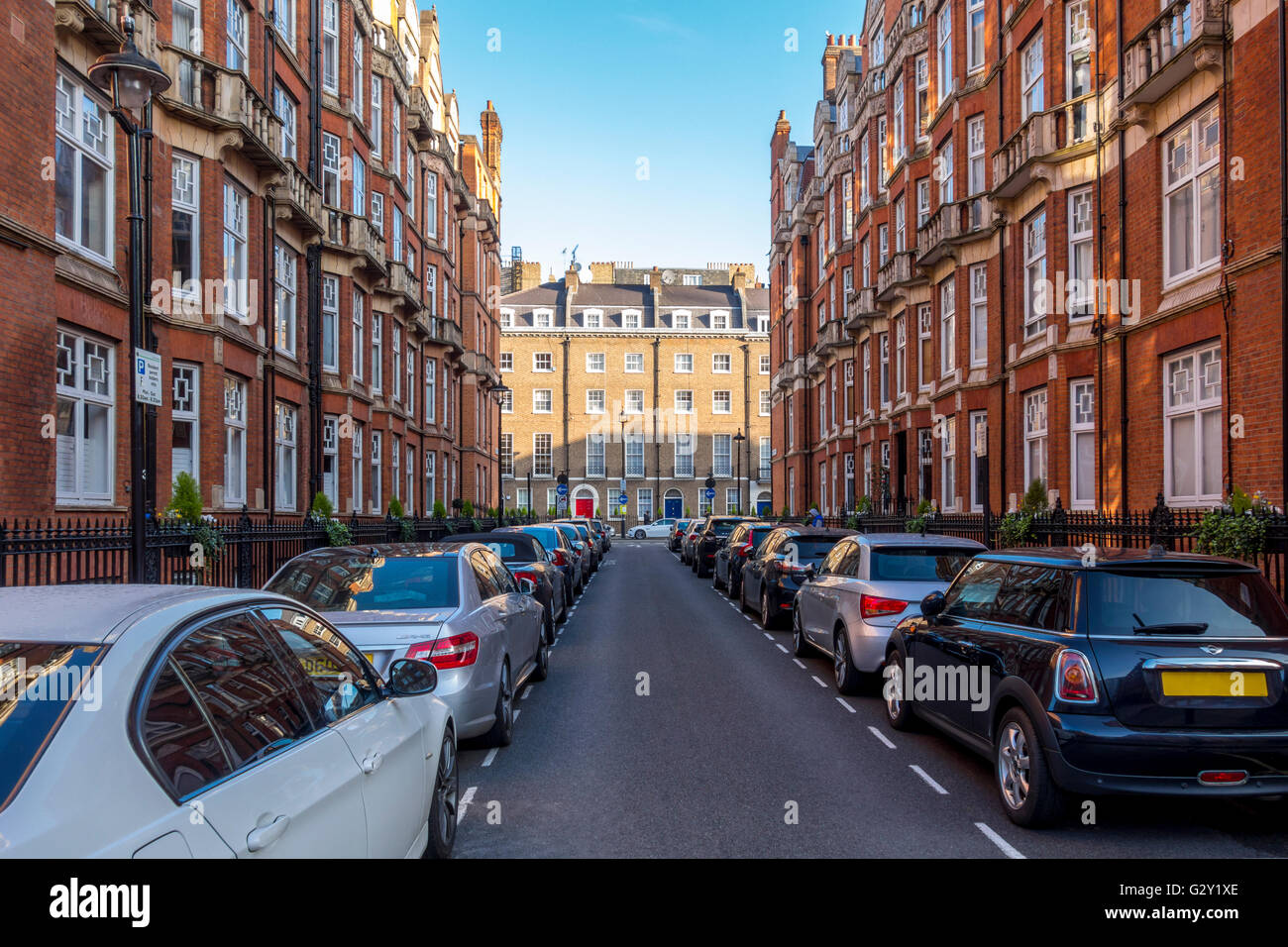 London street with red brick mansion blocks - Stock Image