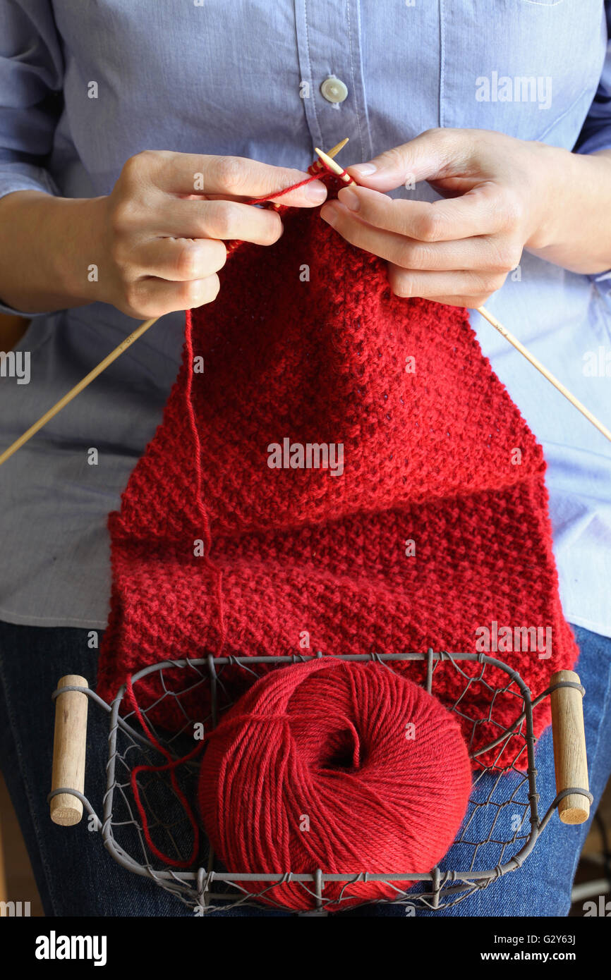 woman hands knitting red woolen scarf - Stock Image