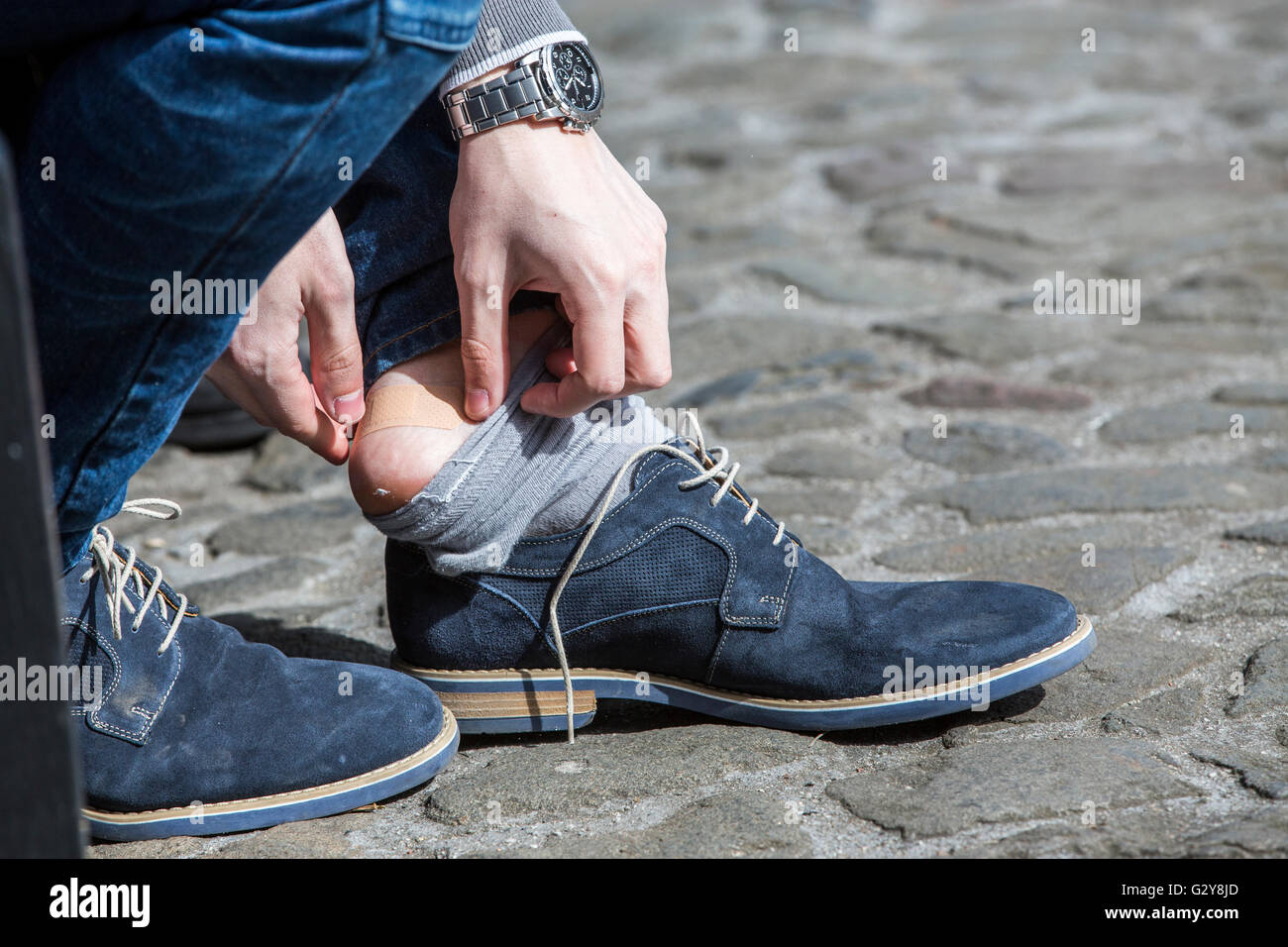 EDINBURGH, UK - 24 APRIL 2016.  Man putting plaster on heel to protect blister caused by new shoes. - Stock Image