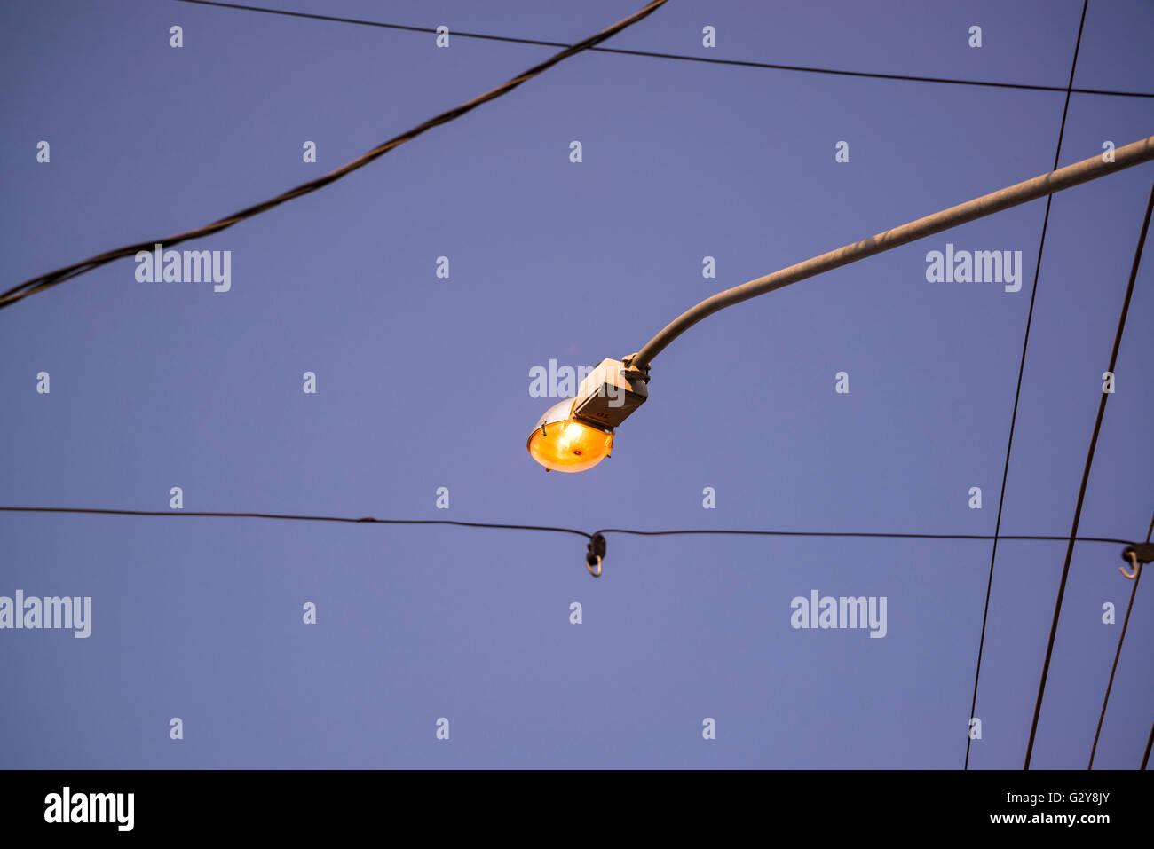 Lit street lamp in daylight - Stock Image