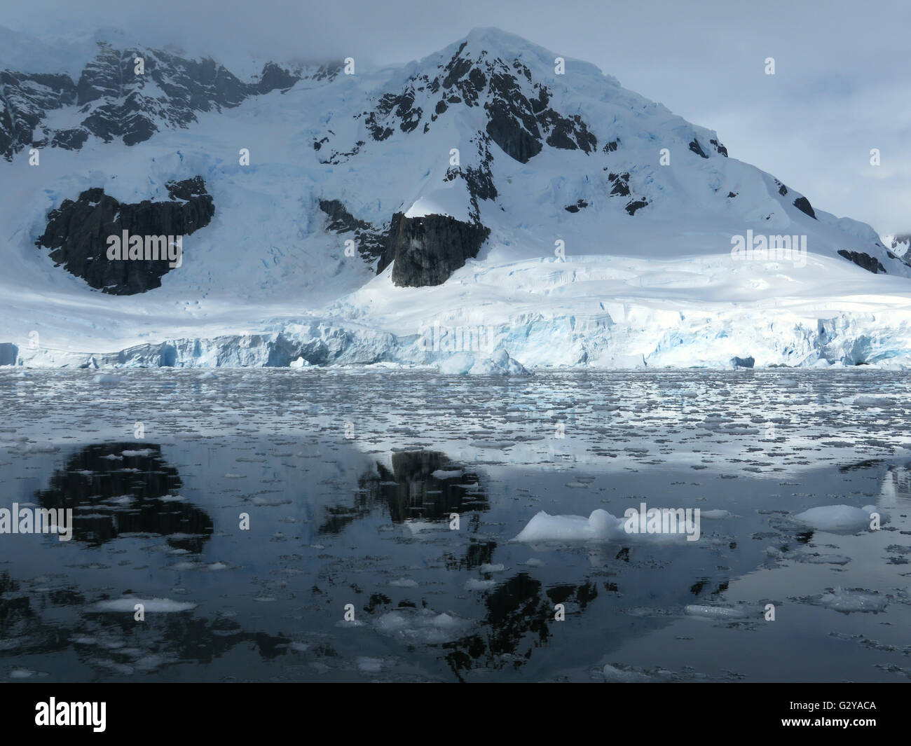 Antarctic mountain and sea shelves reflecting in the ocean waters - Stock Image
