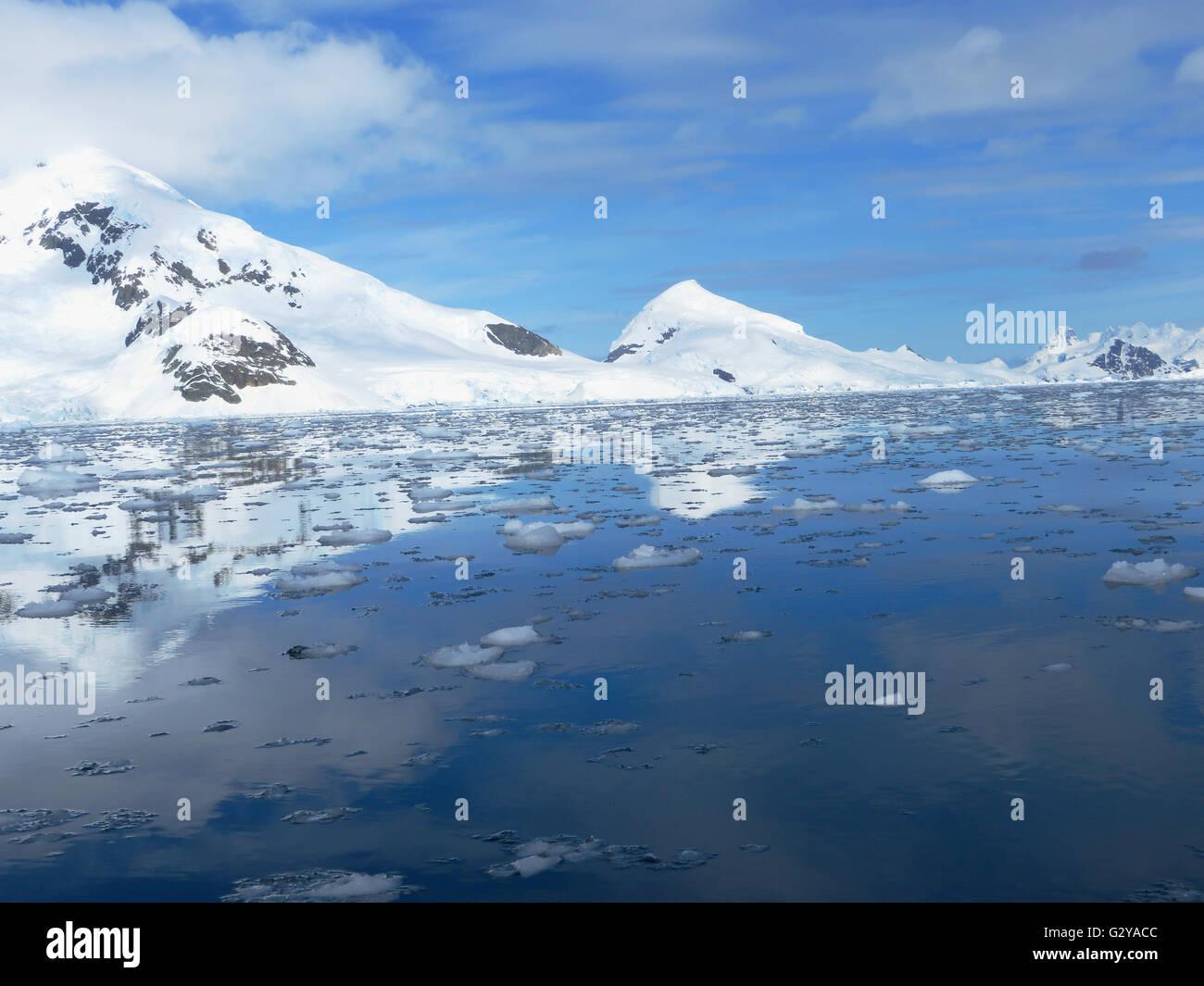 Antarctic mountains and melting sea ice at Port Lockroy region of the Antarctic Peninsula - Stock Image