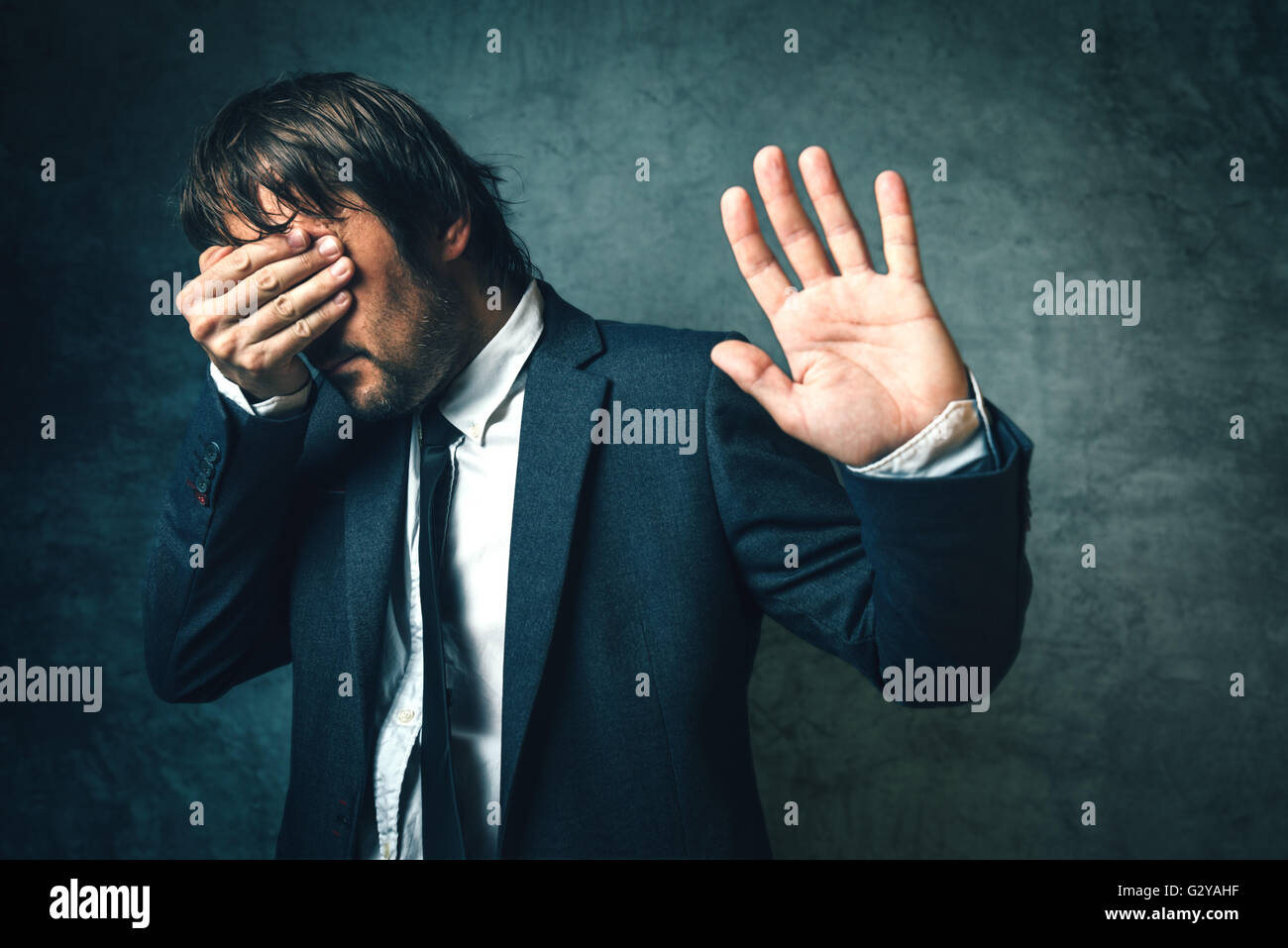 Crooked politician hiding face from newspaper photographers after political scandal,  public embarrassment, hand - Stock Image
