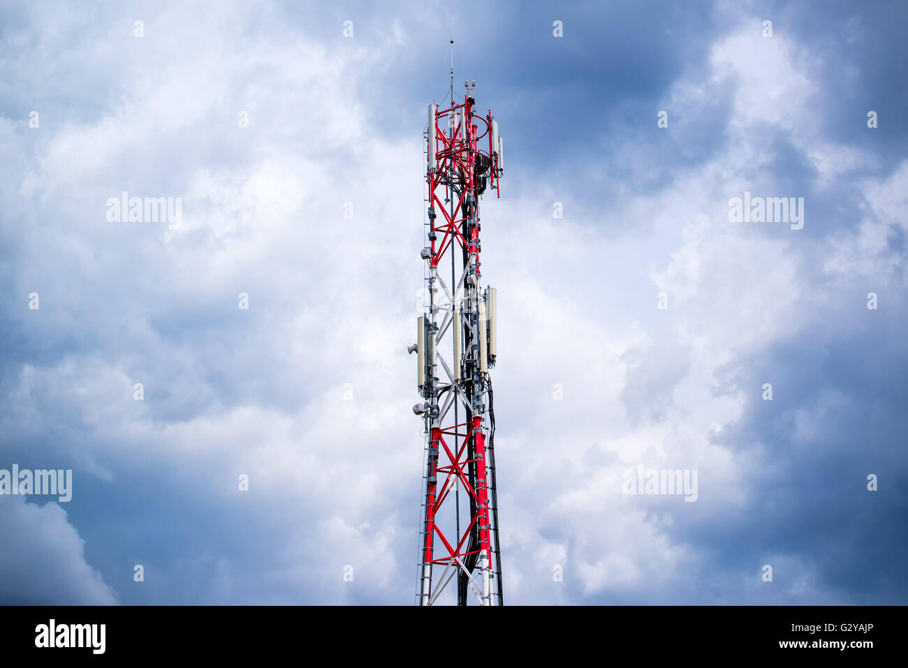 Mobile phone network GSM communication repeater antenna against cloudy sky - Stock Image