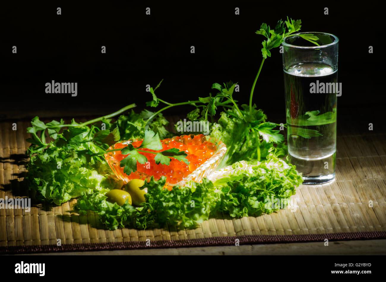 Still life with vodka, caviar, black bread, green olives, herbs and black bread - Stock Image