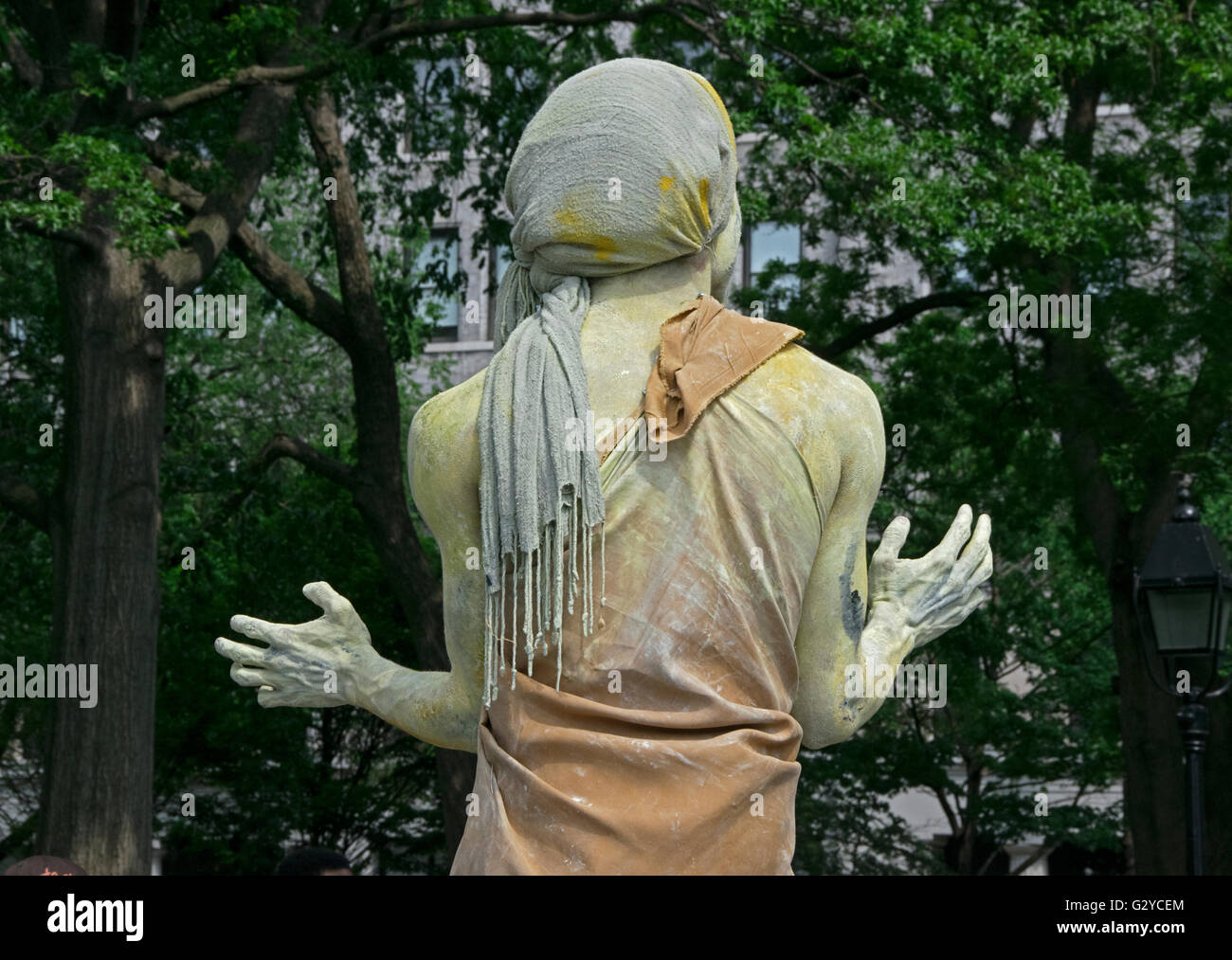 Rear view of mime who stands very still and is covered in chalk & wearing burlap. In Washington Square Park - Stock Image