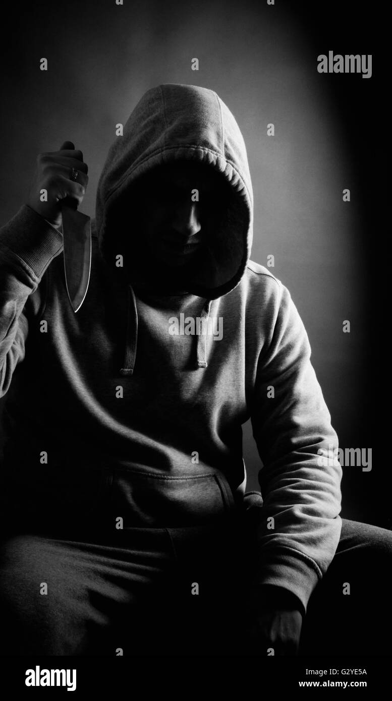 Intimidating hooded male holding a knife - Stock Image