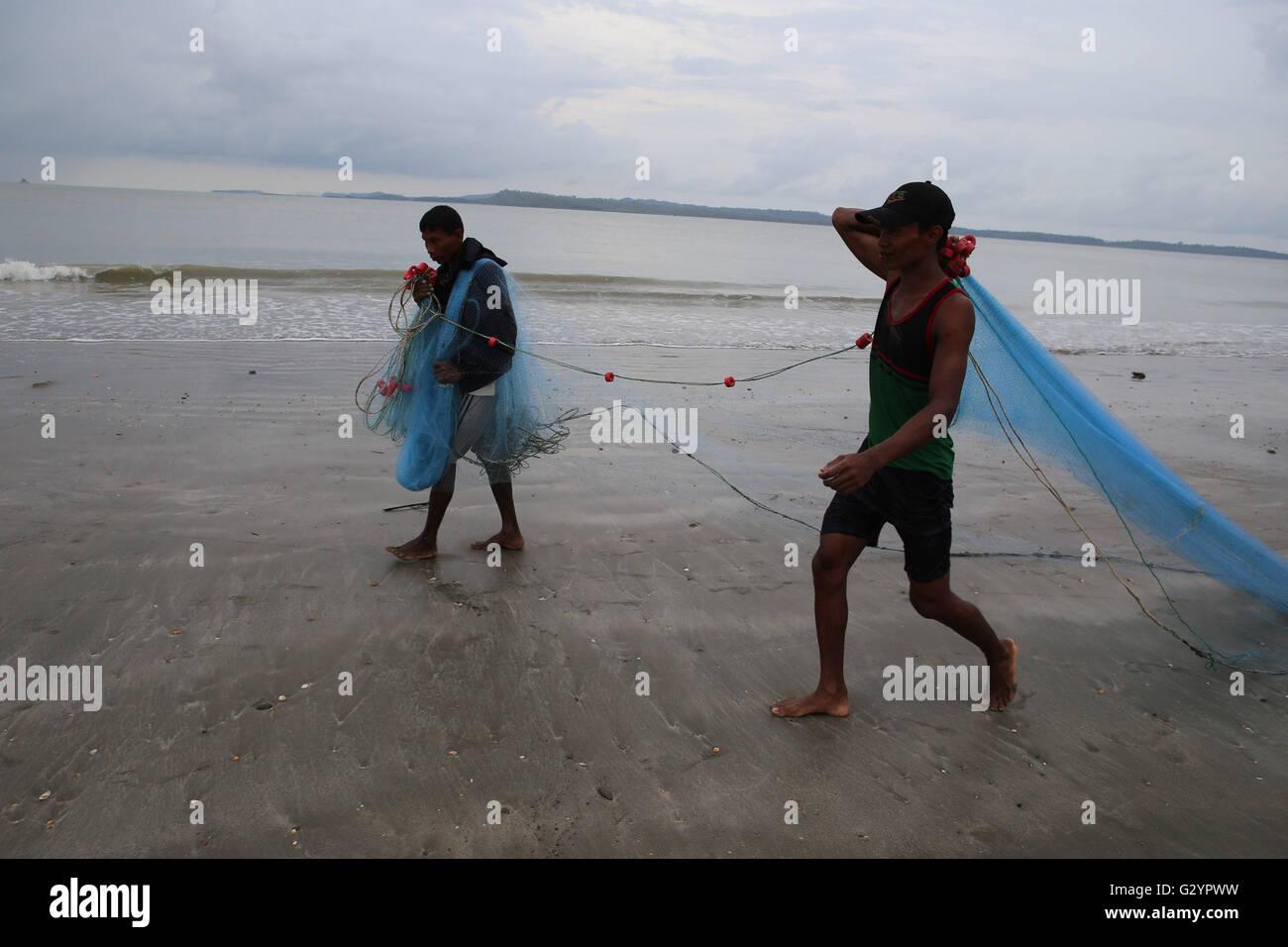 Kyaukphyu, Myanmar. 5th June, 2016. Fishermen carry the fishing net at the Kyaukphyu beach in Rakhine State, western - Stock Image
