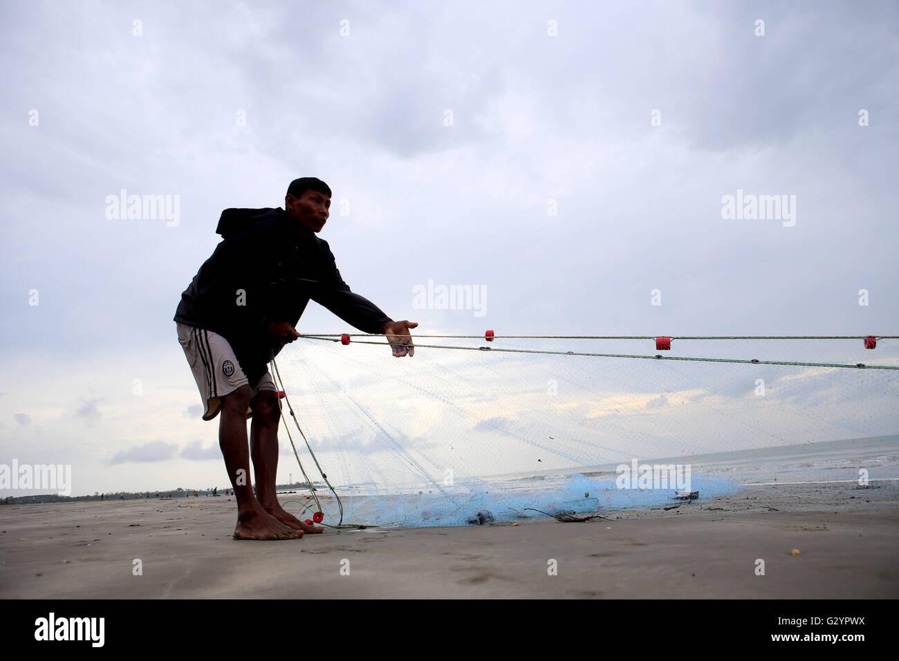Kyaukphyu, Myanmar. 5th June, 2016. A fisherman pulls fishing net at the Kyaukphyu beach in Rakhine State, western - Stock Image