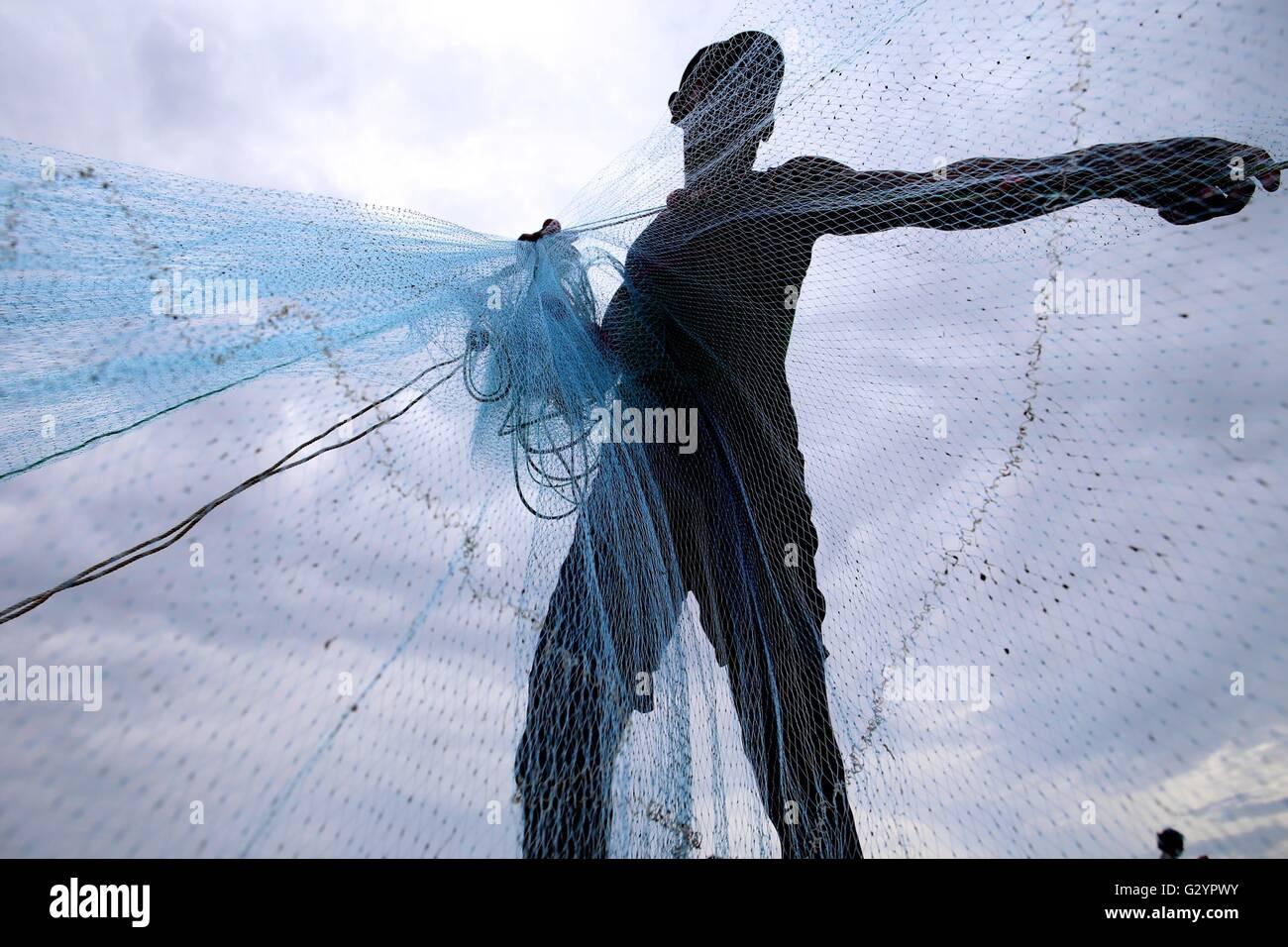 Kyaukphyu, Myanmar. 5th June, 2016. A fisherman prepares his fishing net at the Kyaukphyu beach in Rakhine State, - Stock Image
