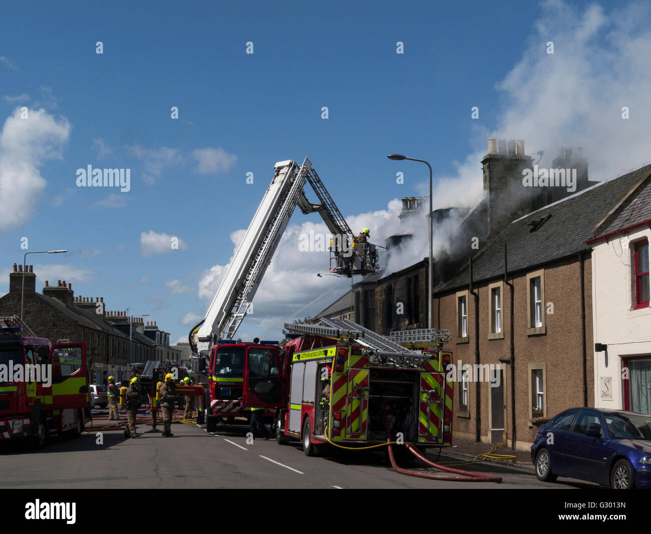 Firemen on extendable ladder tackling a fierce fire premises long standing local business on main street Elie Fife - Stock Image