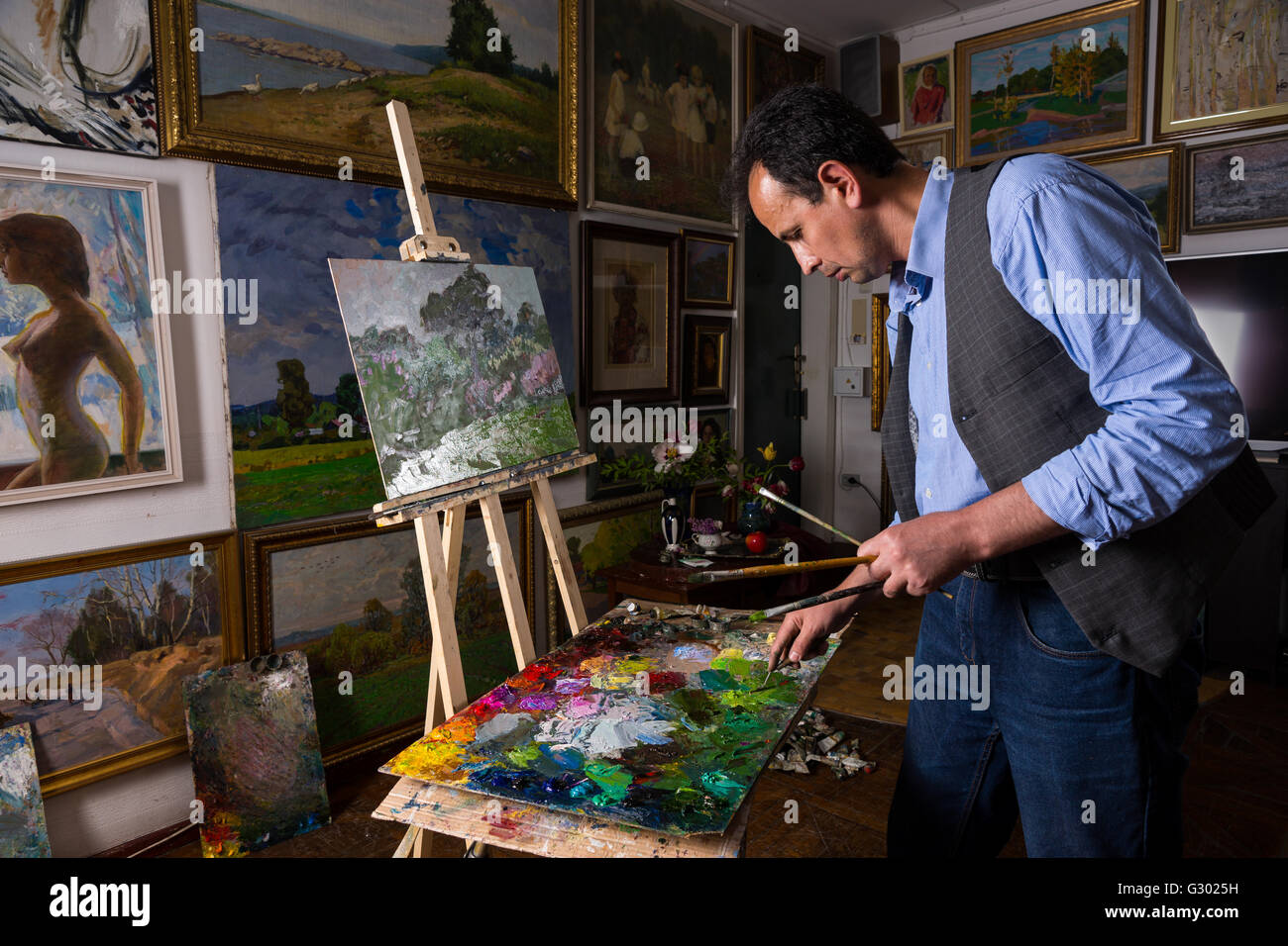 Pensive male painter holding professional paintbrushes and mixing paint by paletteknife on the colorful palette Stock Photo