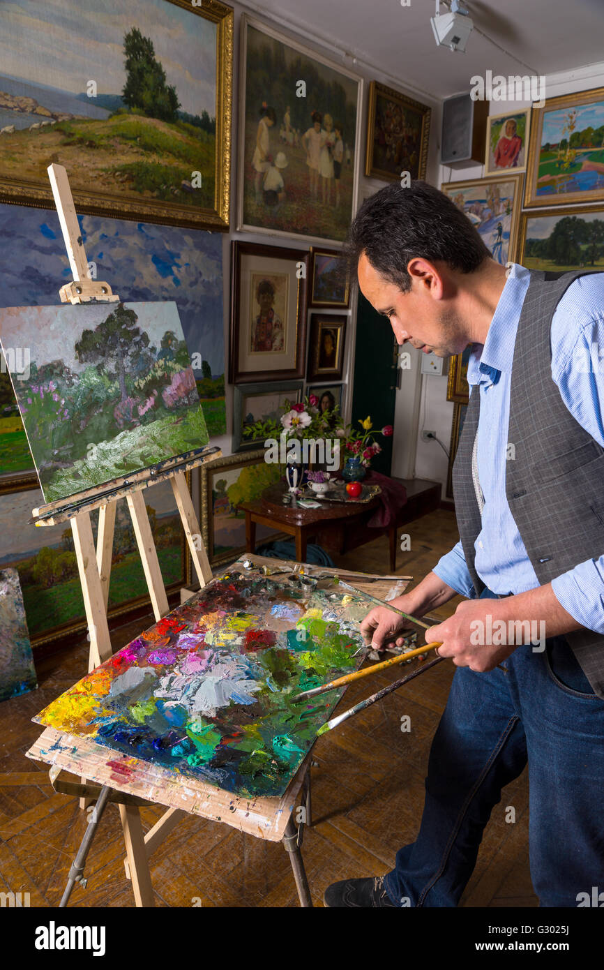 Pensive male artist holding professional paintbrushes and mixing paint by paletteknife on the colorful palette of Stock Photo