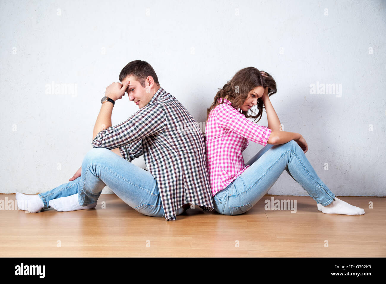Couple sitting with their backs turned after having an argument - Stock Image
