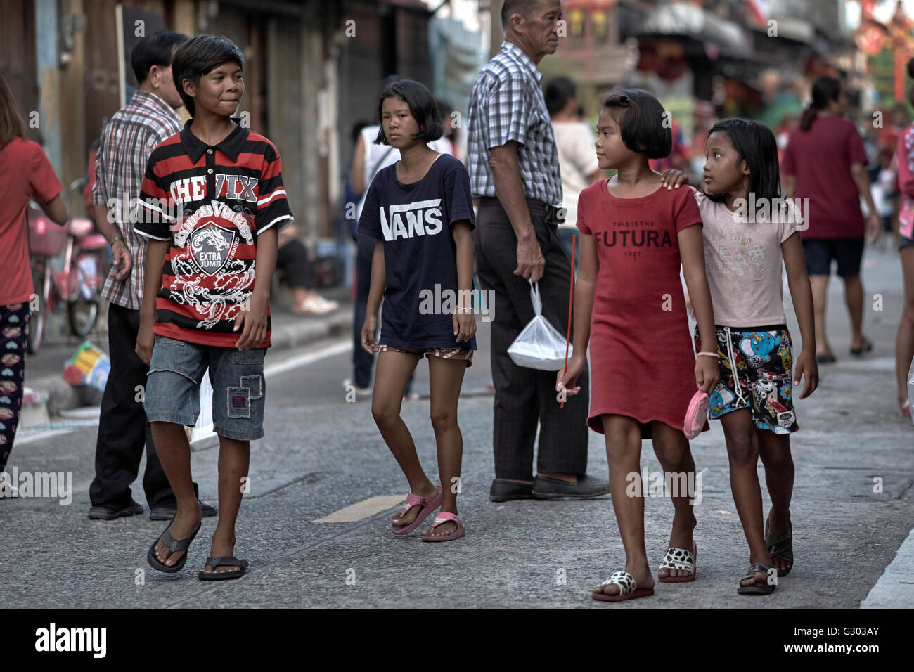 Asian street scene with young boy and girl interacting. Thailand S. E. Asia