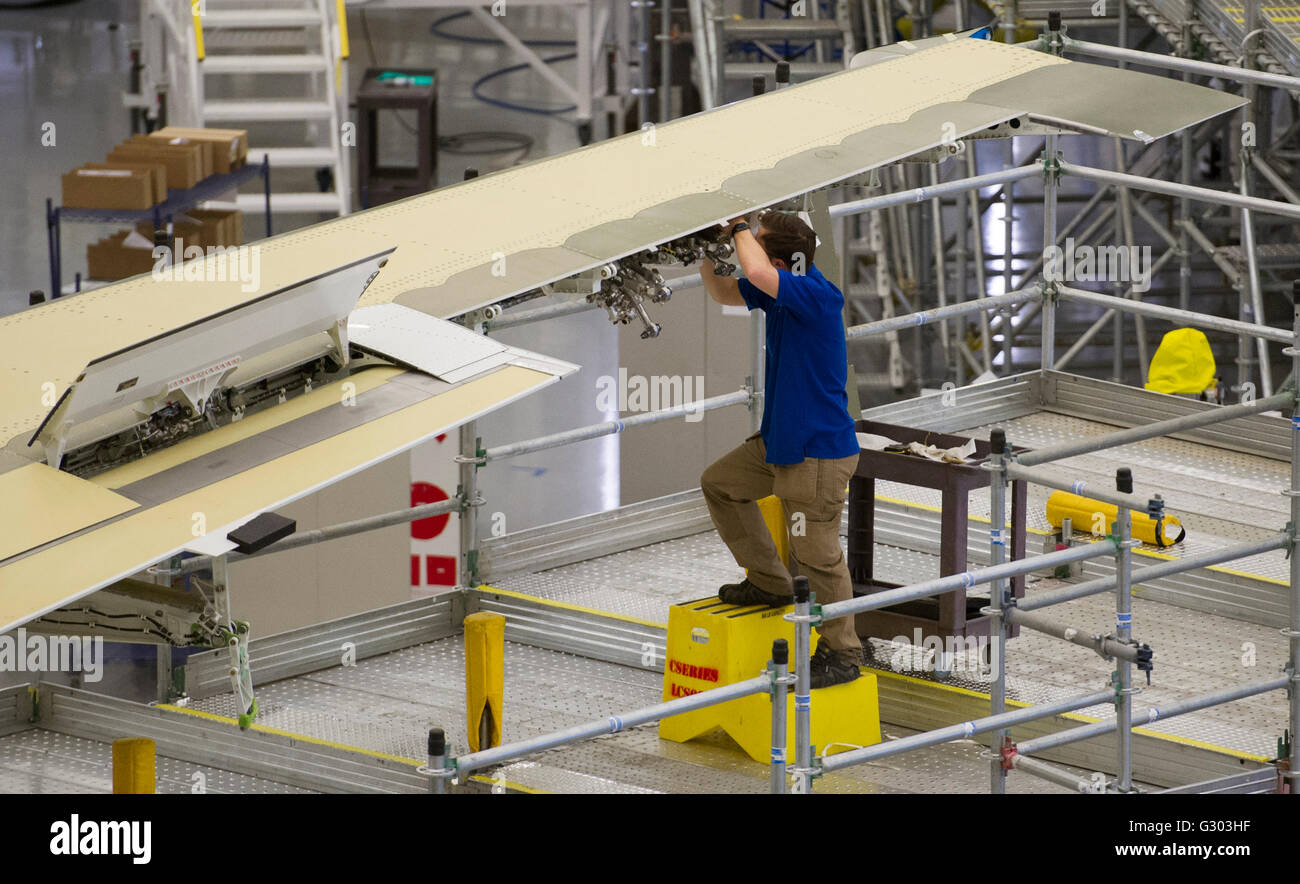 A Bombardier employee works on the wing of a C Series jet on the assembly line at a Bombardier assembly plant in - Stock Image