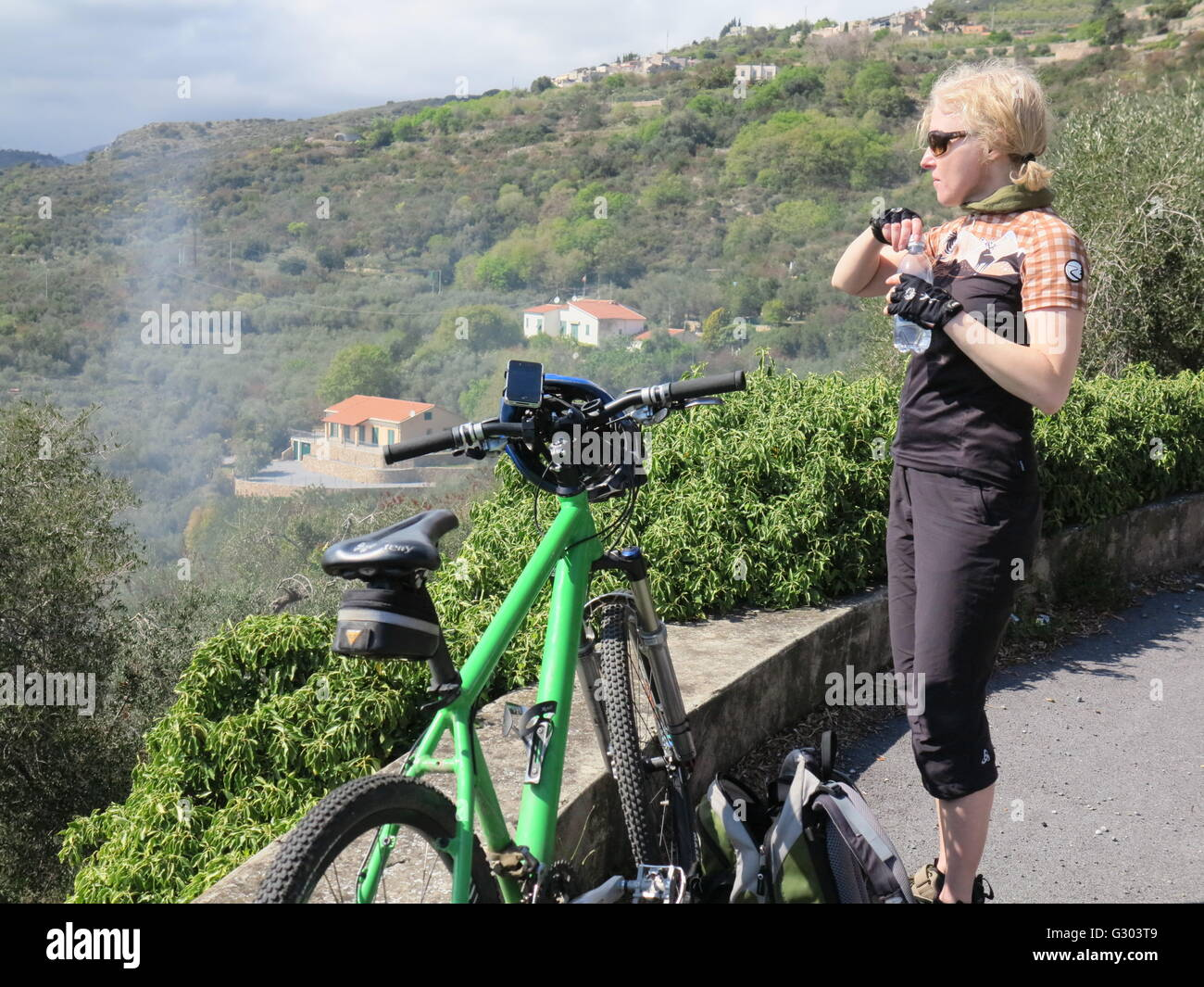 Woman taking a refreshment from a water bottle during a mountain bike ride on the Italian Riviera, Liguria, Italy, - Stock Image