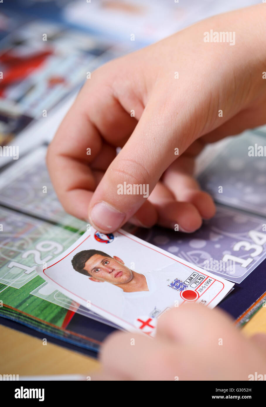 A boy putting Panini football stickers in to an album - Stock Image