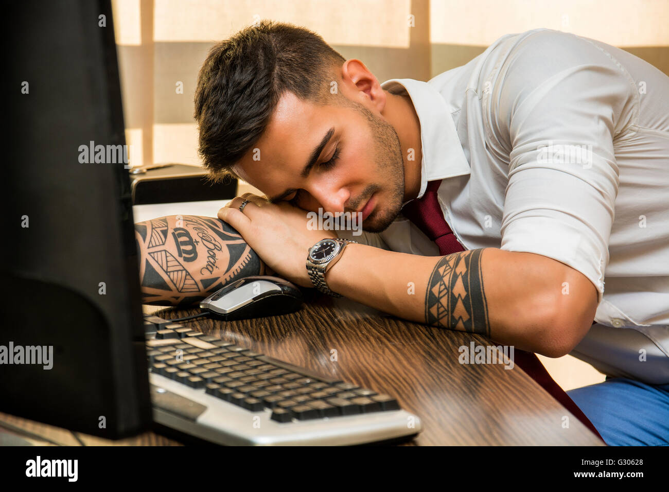 Overworked, tired young businessman sleeping on his desk in office, in front of computer - Stock Image