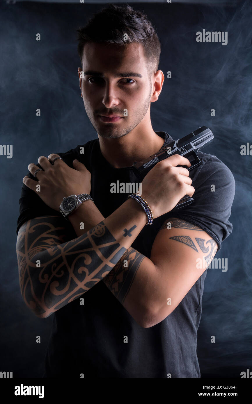 Young handsome man holding a hand gun, wearing black t-shirt, arms crossed on chest, on dark background in studio Stock Photo