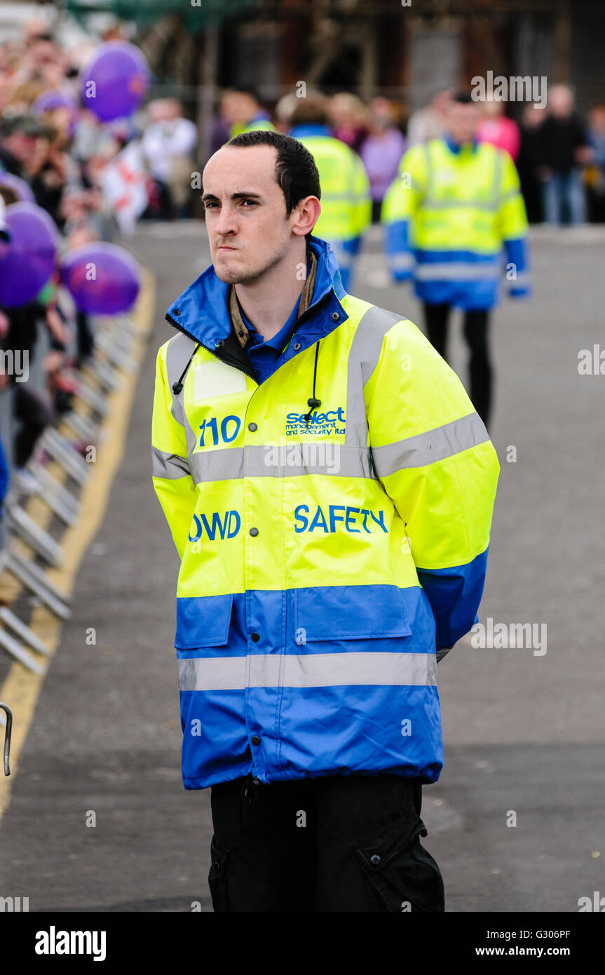 Select Security crowd control steward keeping an eye on the crowd's safety - Stock Image