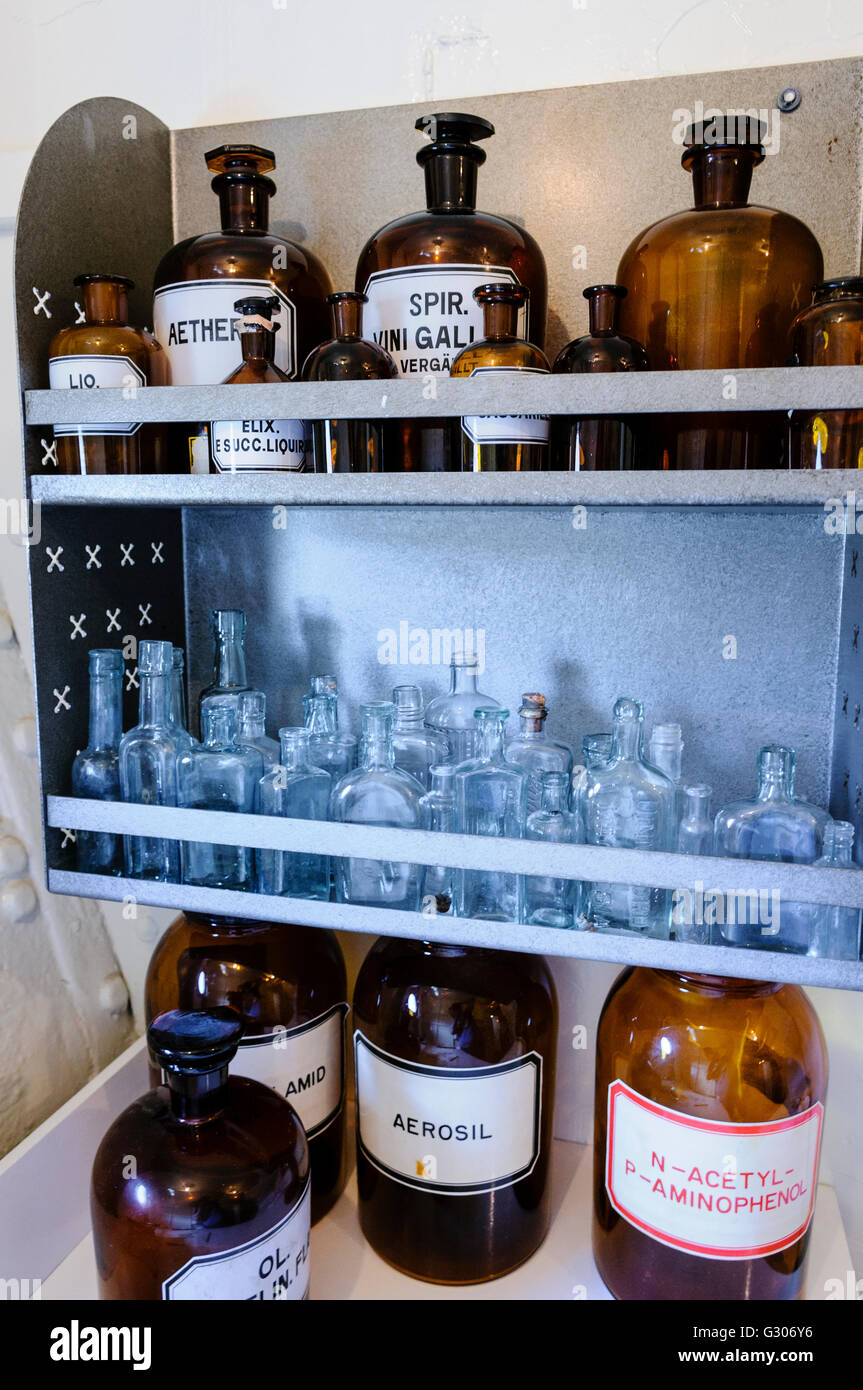 Bottles on shelves within a doctor's surgery from WW1. - Stock Image