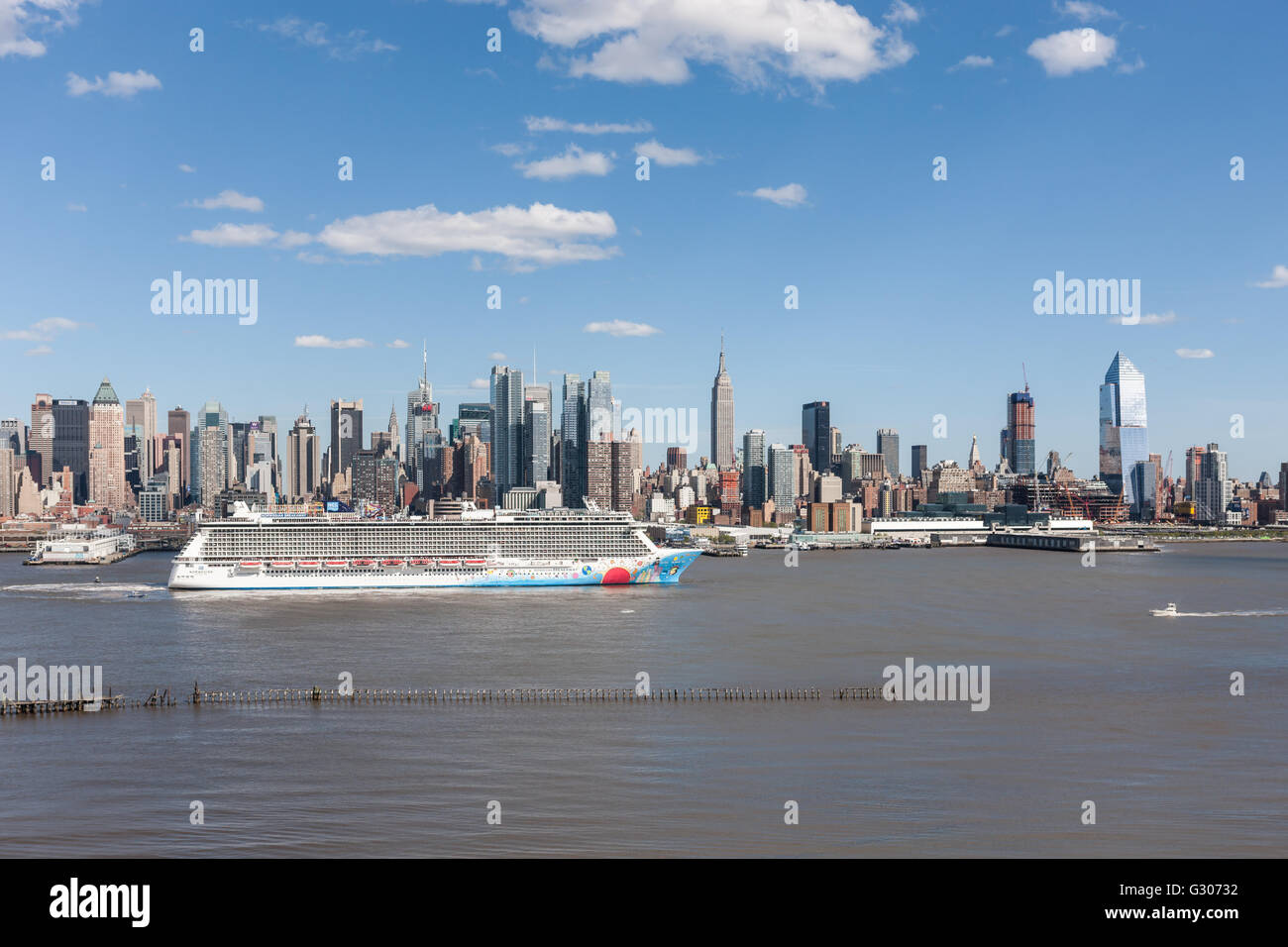 Cruise ship Norwegian Breakaway heads south on the Hudson River past the mid-town skyline of New York City. - Stock Image