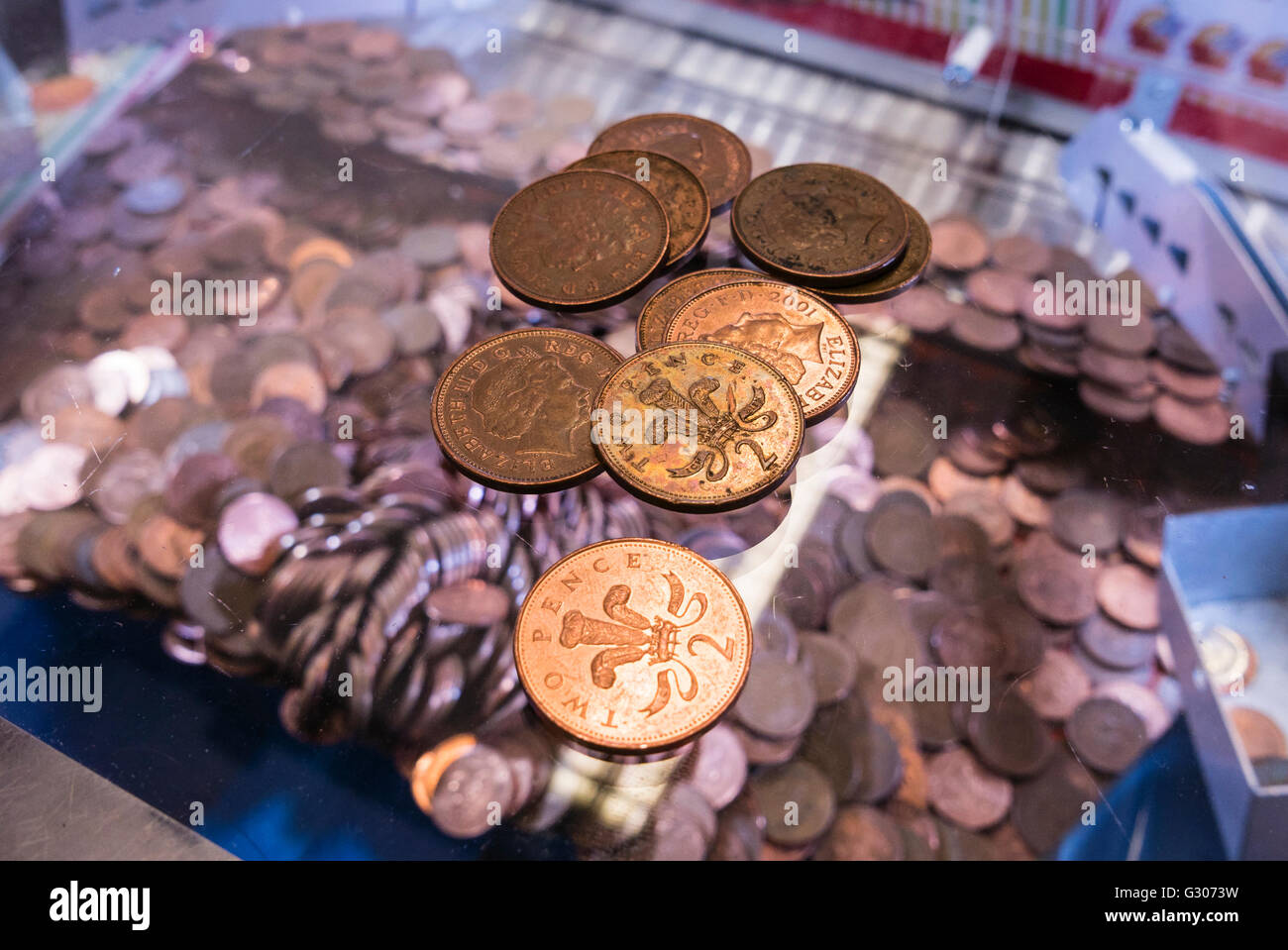 Two-pence coins lie on the glass on top of a 2p nudger machine in a seaside amusement arcade. - Stock Image