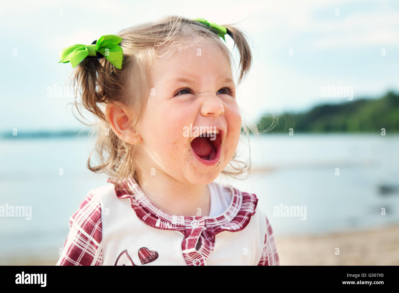 Funny little girl shouting at the sea - Stock Image