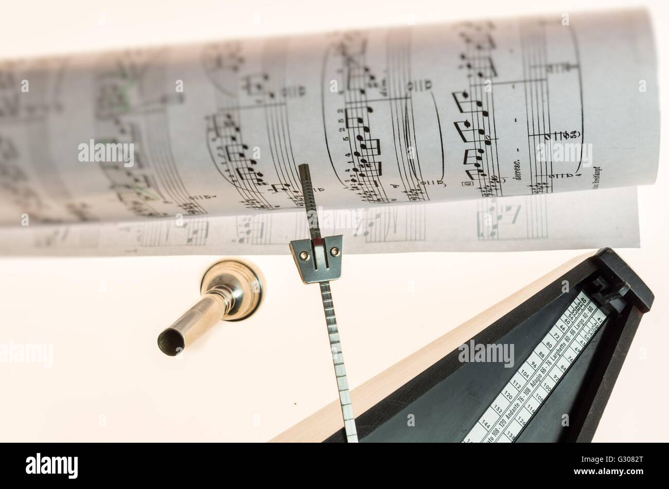 Metronome and mouthpiece of a trumpet isolated on a blank white background  as copy space - Stock Image