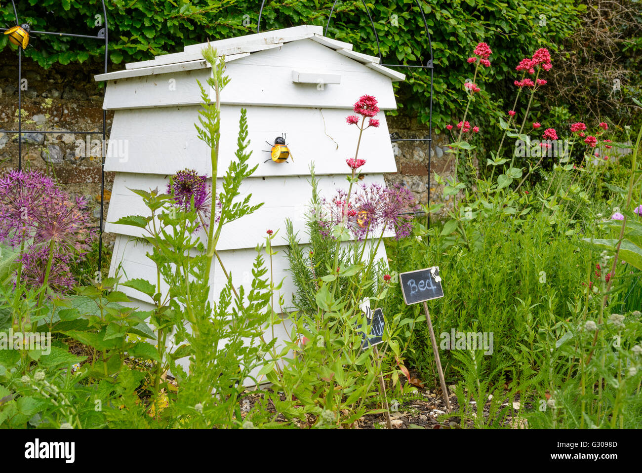 White wooden beehive in a garden. - Stock Image