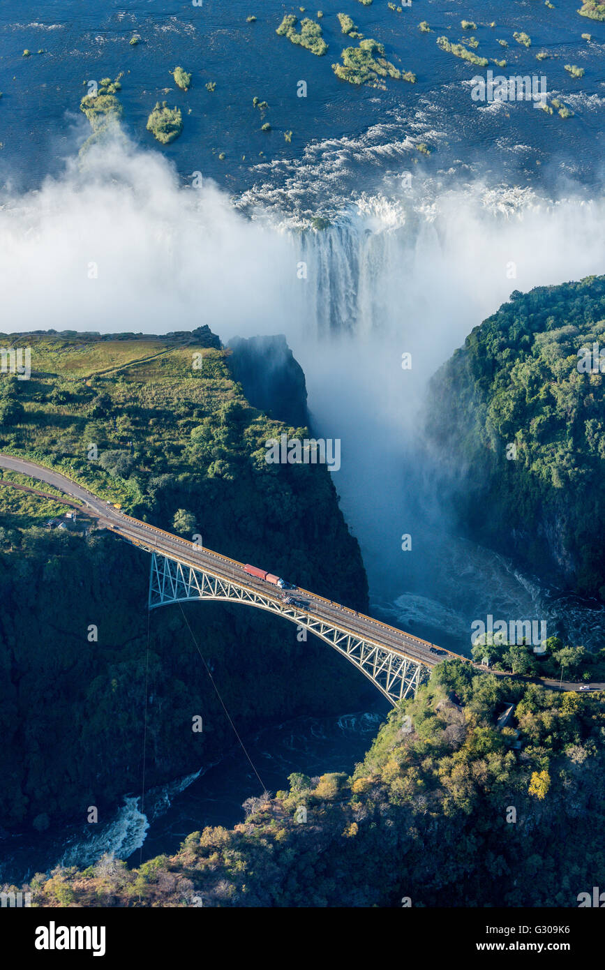 Aerial view of Victoria Falls behind bridge - Stock Image