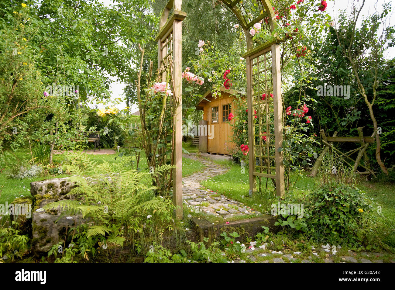 Garden idyll with a garden shed and rose arch with blooming red roses - Stock Image