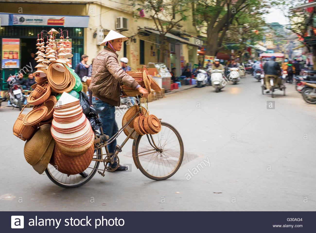 Man on bicycle selling Vietnamese hats in Old Quarter, Hoan Kiem District, Hanoi, Vietnam, Indochina, Southeast Stock Photo