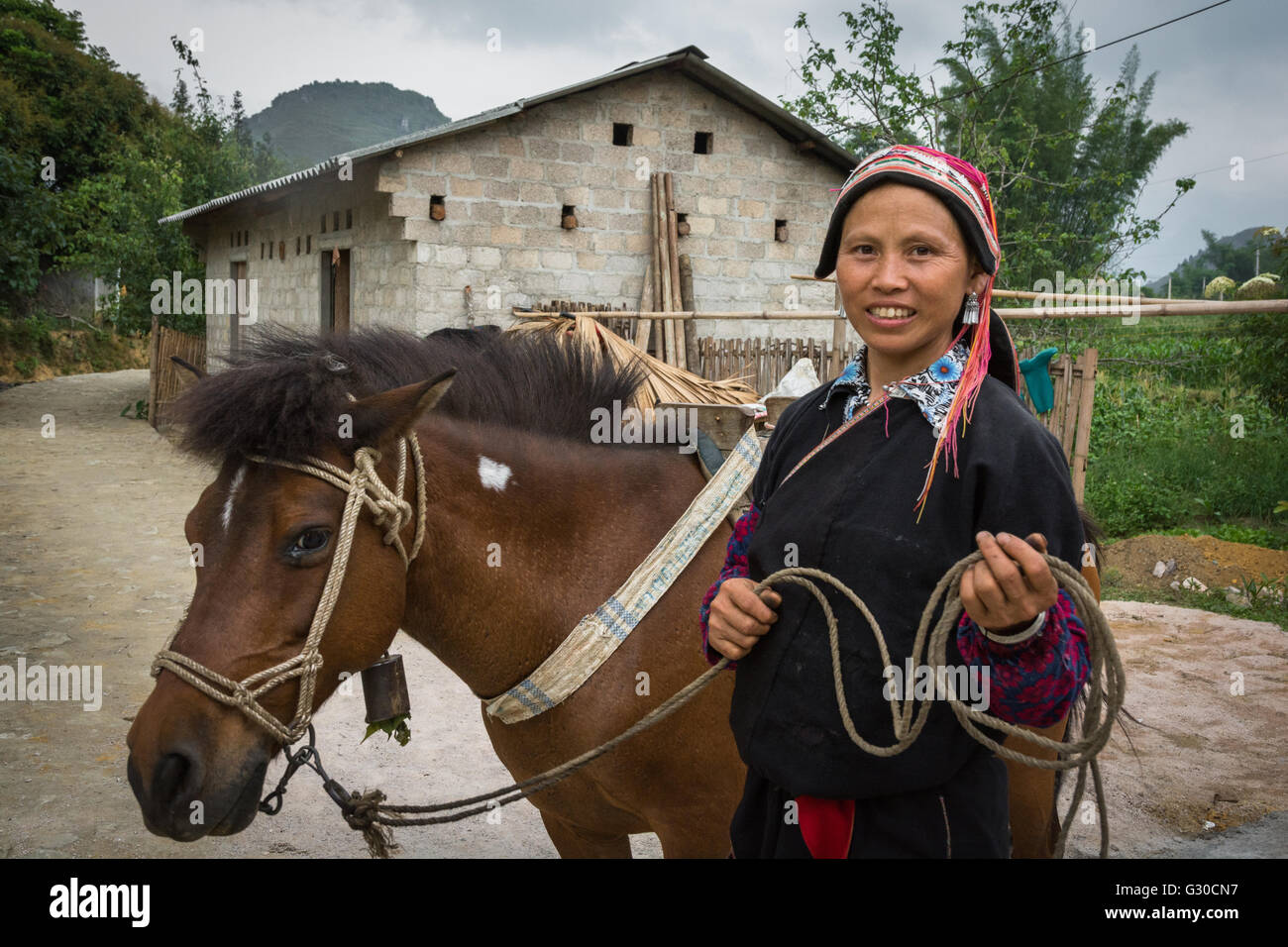 Red Dao woman and her horse on the farm of the Ly Dai Duyen Guest House, Nam Dan, Ha Giang Province, Vietnam. Stock Photo