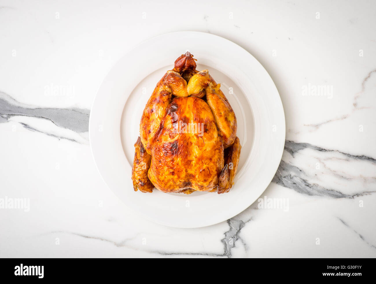 Rotisserie Chicken. Whole roast chicken on white plate seen from above on marble work surface - Stock Image